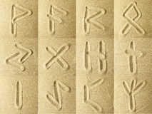 Runes Written in the Sand. Golden colors Royalty Free Stock Images