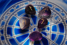 Runes with zodiac. Amethyst with runes symbols over a zodiac wheel royalty free stock photos