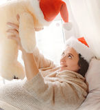 Runette woman relaxing near window and playing with toy bear wea Royalty Free Stock Photography