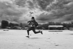 runing在海滩的商人 背景迷离弄脏了抓住飞碟跳的行动 库存照片