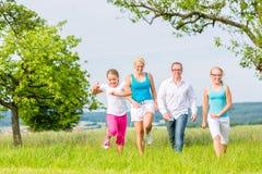 runing在领域或草坪的家庭在夏天 免版税图库摄影