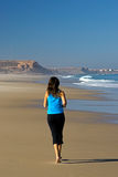 Runing in the beach. Young athletic woman doing exercise royalty free stock image