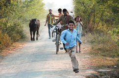Runing Child. Photograph of a Runing Child to see a photographer, His Father and sister also happy in background.rnHe\'s father are farmer and come back from Stock Photos