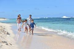 Runinng de la familia de cuatro miembros en la playa en las zonas tropicales Foto de archivo libre de regalías