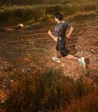 Runner. Moving through sunlit landscape. (contrejour lighting Stock Image