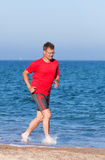 Runner. Happy young man running on the beach Stock Photography