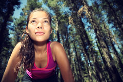 Runner. Woman running in forest taking a break from working out. Beautiful young female athlete - copy space Stock Photography