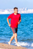 Runner. Happy young man running on the beach Royalty Free Stock Image
