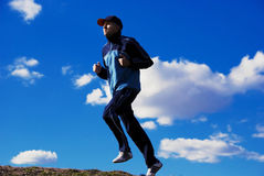 Runner. Man running on a hill crest with blue cloudy sky as background royalty free stock photography