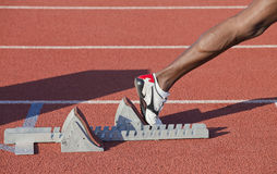 Runner. Close-up image of a male moving leg leaving the starting blocks for a sprint run on a track Royalty Free Stock Photography