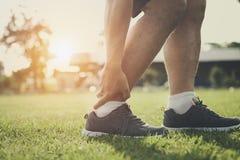 Runner of ankle sprain from running. At park Stock Photos
