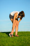 Runner ankle sprain. Sport running ankle sprain. Sportswoman touching painful twisted or broken ankle after exercising off road on grass field. Athlete runner Royalty Free Stock Photography
