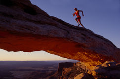 Runner On Arch. Runner on natural arch in desert stock photos