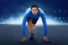 Runner asian man with hands on starting line ready to sprint. On concrete track Stock Photo