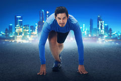 Runner asian man with hands on starting line ready to sprint. On concrete track Royalty Free Stock Photos