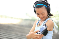 Runner athlete listening to music in headphones from smart phone mp3 player Stock Photography
