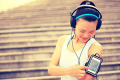 Runner athlete listening to music in headphones from smart phone mp3 player Royalty Free Stock Photo