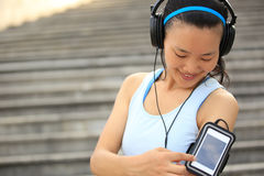 Runner athlete listening to music in headphones from smart phone mp3 player Royalty Free Stock Images