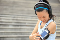 Runner athlete listening to music in headphones from smart phone mp3 player Stock Image