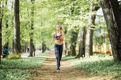 Runner athlete running at cityl park. Young woman fitness jogging workout wellness concept. Runner athlete running at cityl park. woman fitness jogging workout stock image