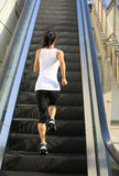 Runner athlete running on escalator stairs Royalty Free Stock Images