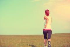 Runner athlete running on grass seaside. Royalty Free Stock Image