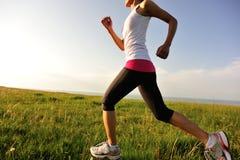 Runner athlete running on grass seaside. Royalty Free Stock Photo