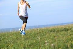 Runner athlete running on grass seaside. Stock Photo