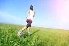 Runner athlete running on grass seaside. Stock Image