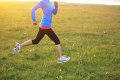 Runner athlete running on grass seaside. Royalty Free Stock Images