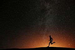 Runner athlete running on the hill with beautiful stars royalty free stock images