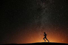 Runner athlete running on the hill with beautiful starry night stock images