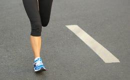 Runner athlete running legs on city road Stock Image