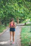 Runner athlete running at park. woman fitness jogging workout wellness concept. Runner athlete running at tropical park. woman fitness jogging workout wellness royalty free stock photos