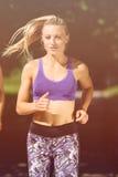Runner athlete running at park. woman fitness jogging workout wellness concept. Runner athlete running at tropical park. woman fitness jogging workout wellness stock images