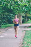 Runner athlete running at park. woman fitness jogging workout wellness concept. Runner athlete running at tropical park. woman fitness jogging workout wellness royalty free stock image