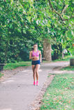Runner athlete running at park. woman fitness jogging workout wellness concept. Runner athlete running at tropical park. woman fitness jogging workout wellness royalty free stock photo