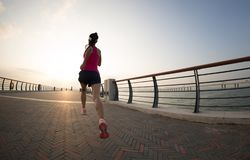 Woman running on seaside trail stock image