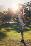 Runner athlete stretching legs outdoors in a park Royalty Free Stock Photos