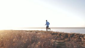 Runner athlete training. Young male trai runner training outdoors in autumn time alone stock footage