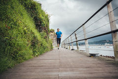 Runner. Attractive man running on a wooden walkway next to the sea in a stormy day. Lonely daily training Royalty Free Stock Photos