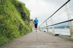 Runner. Attractive man running on a wooden walkway next to the sea. Daily training Stock Photo