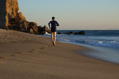 Runner on Beach Shore. Man running along the shore of Pointe Dume Beach in Malibu, Ca Stock Photos