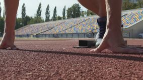 Runner beginning his sprint from starting blocks, crouch start, training stock footage