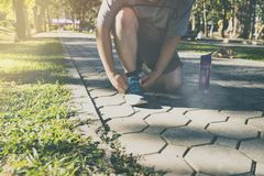 The runner bent down to tie the shoe in park. Royalty Free Stock Images