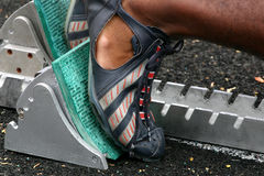 Runner in blocks at track meet. Closeup of a runners track shoes as he places his feet in the starting blocks for a race Royalty Free Stock Image