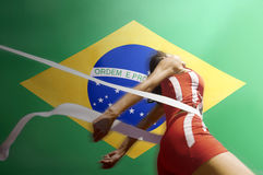Runner Breaking through the finishing line tape over Brazilian flag Royalty Free Stock Photos
