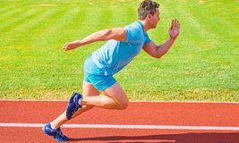 Runner captured in motion just after start of race. Runner sprint race at stadium. Boost speed concept. Man athlete. Runner push off starting position stadium royalty free stock photography