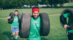 Runner carrying tires in a test of extreme obstacle race Royalty Free Stock Photo