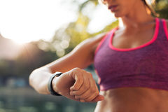 Runner checking her fitness smart watch device stock images
